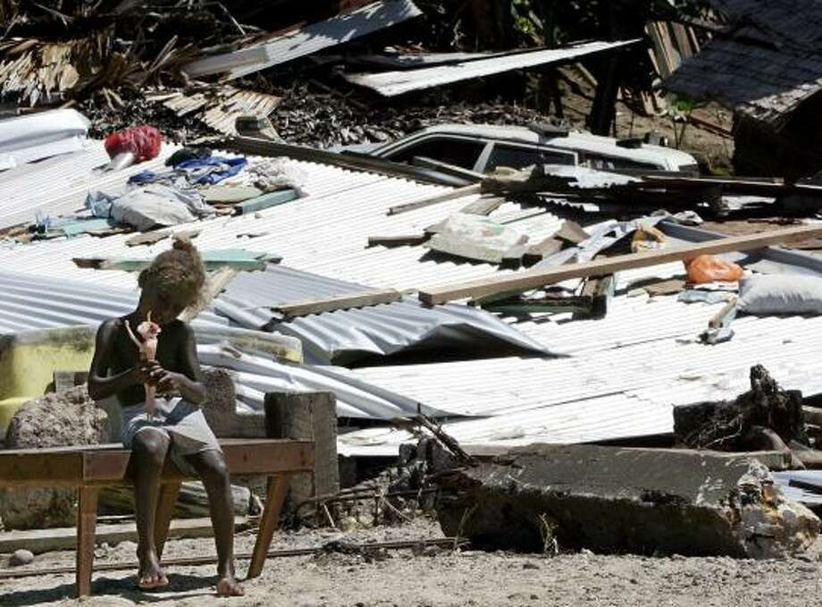 A small girl sits in front of a tsunami-flattened house Thursday in Gizo, Solomon Islands. Photo: ROB GRIFFITH, ASSOCIATED PRESS