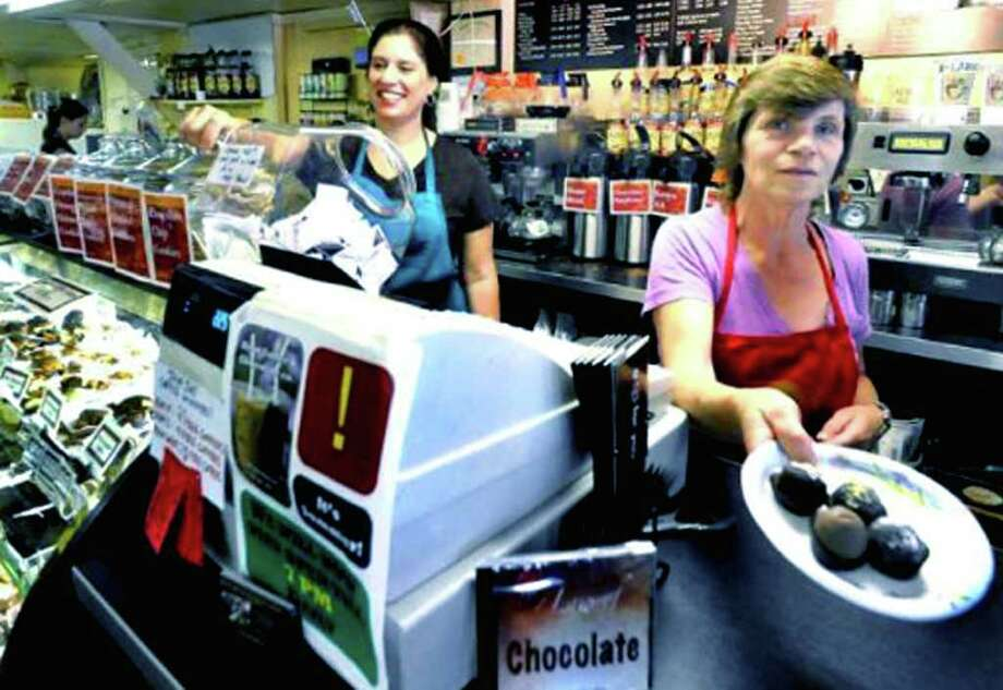 SPECTRUM/Darlene Decker dishes out chocolate to a patron of the Kent Coffee & Chocolate Company as shop owner Sandra Champlain goes about her work with a smile. July 2011 Photo: Michael Duffy