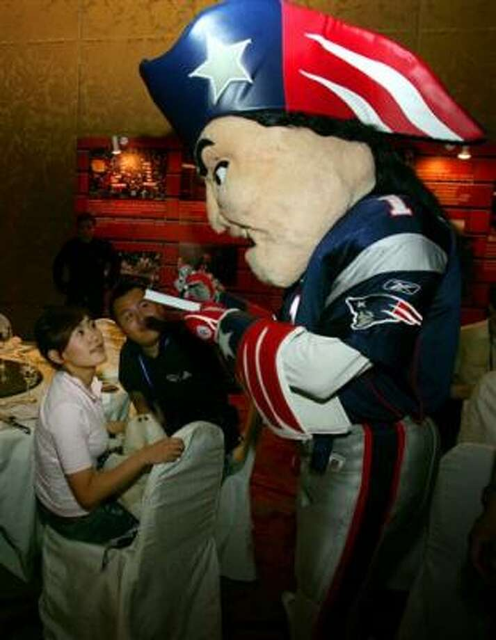"New England Patriots mascot ""Pat'' signs autographs Friday in Beijing during the New England Patriots' China Tour. An NFL exhibition game is tentatively set to be played in Beijing in 2009. Photo: Elizabeth Dalziel, AP"