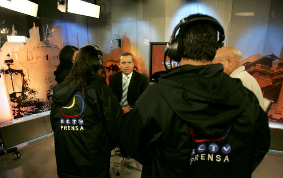 TV journalist Miguel Angel Rodriguez, center, chats with technicians Monday at the studios of Radio Caracas TV, a frequent critic of Hugo Chavez. Chavez says the station's license won't be renewed. Photo: Fernando Llano, AP