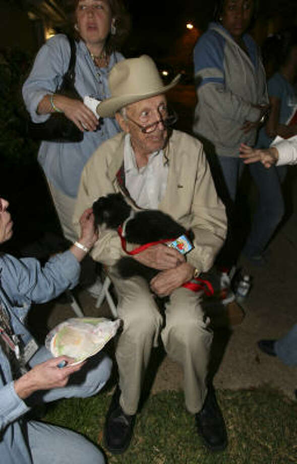 Leland Shumate is reunited with his cat, Cookie, who ran off as he and his wife, Mabel, evacuated their apartment that went up in flames Friday night in Katy. Photo: KAREN WARREN, Chronicle