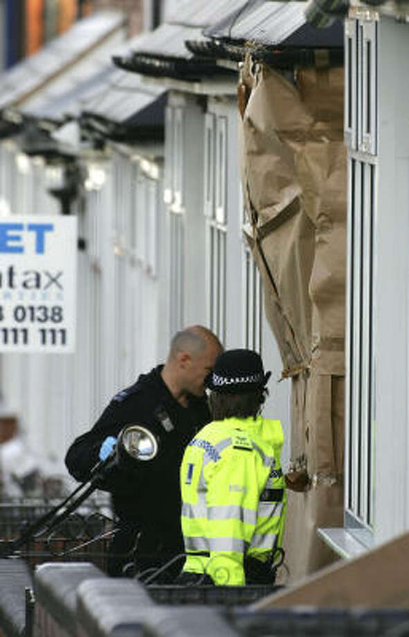 A forensic officer enters a house Wednesday in Birmingham, England, where the windows were covered by paper. Police cordoned off 12 houses and two Islamic bookshops and several other businesses in a Birmingham neighborhood heavily populated by Pakistanis and other Asians. Photo: Christopher Furlong, Getty Images
