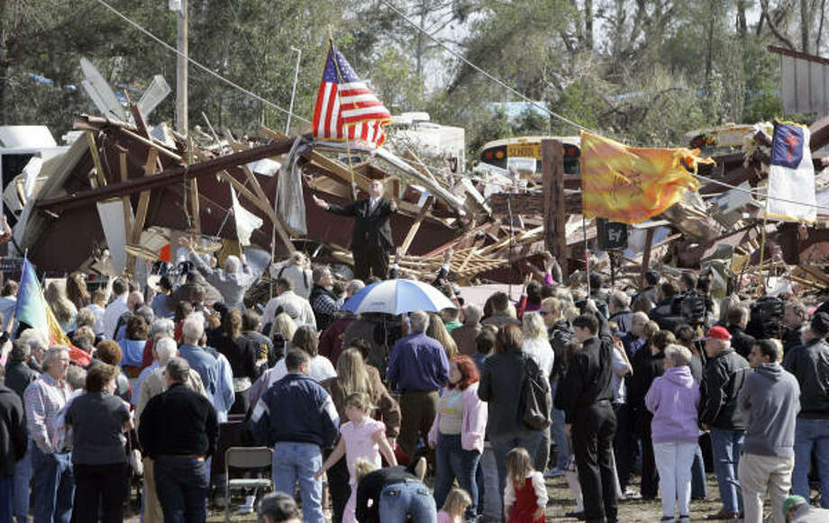 Facing the crowd, Larry Lynn, pastor of the Lady Lake Church of God, speaks during a service Sunday where the church used to stand in Lady Lake, Fla. The church was destroyed by a tornado that struck the area early Friday and killed 20 people. Photo: John Raoux, AP