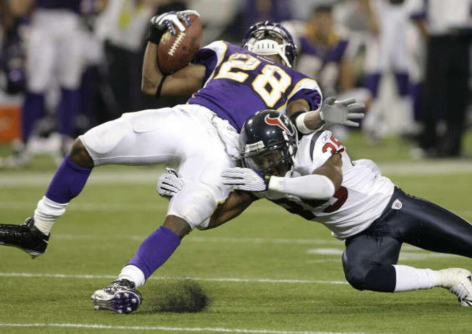 Minnesota Vikings running back Adrian Peterson is hit by Houston Texans cornerback Jacque Reeves. Photo: Brett Coomer, Chronicle