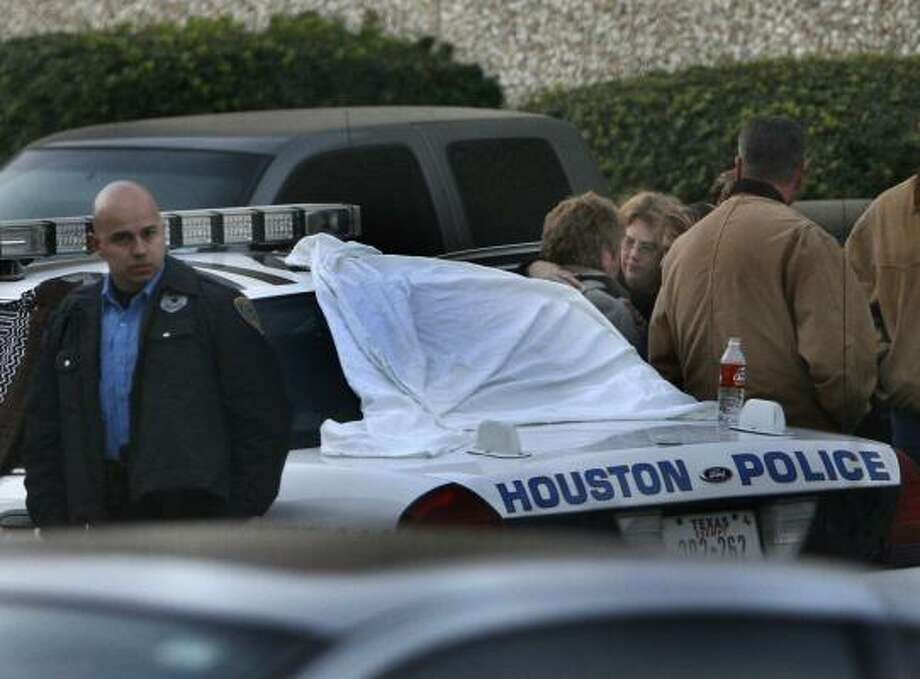 A group of people tries to comfort an unidentified woman whose husband was shot to death Wednesday afternoon by an employee at Service Wire Co. on Houston's northeast side. Photo: CARLOS ANTONIO RIOS, CHRONICLE