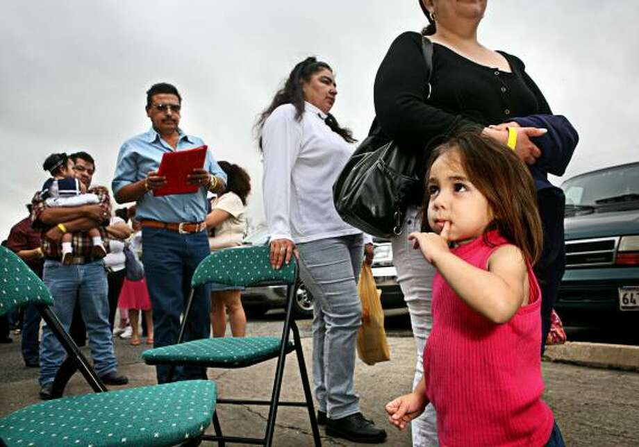 Melissa Villarreal, 2, waits with her mother, Yadira Villarreal, at Milby High School, where citizenship applications were distributed. Photo: ERIN TRIEB, FOR THE CHRONICLE