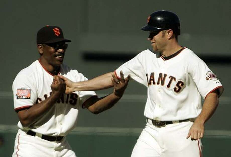 Giants first base coach Willie Upshaw, left, congratulates San Francisco rookie Nate Schierholtz after the latter's game-winning RBI single in the 13th inning Saturday against the Yankees. Photo: BEN MARGOT, ASSOCIATED PRESS