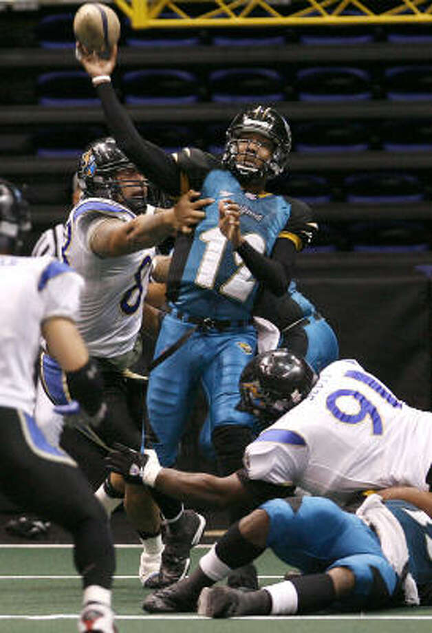 Texas Copperheads quarterback Kenton Evans manages to fire off a pass before being taken out by two Lubbock Renegade defenders at the Berry Center Saturday night. The Copperheads lost the game 77-44. Photo: Diana L. Porter, For The Chronicle