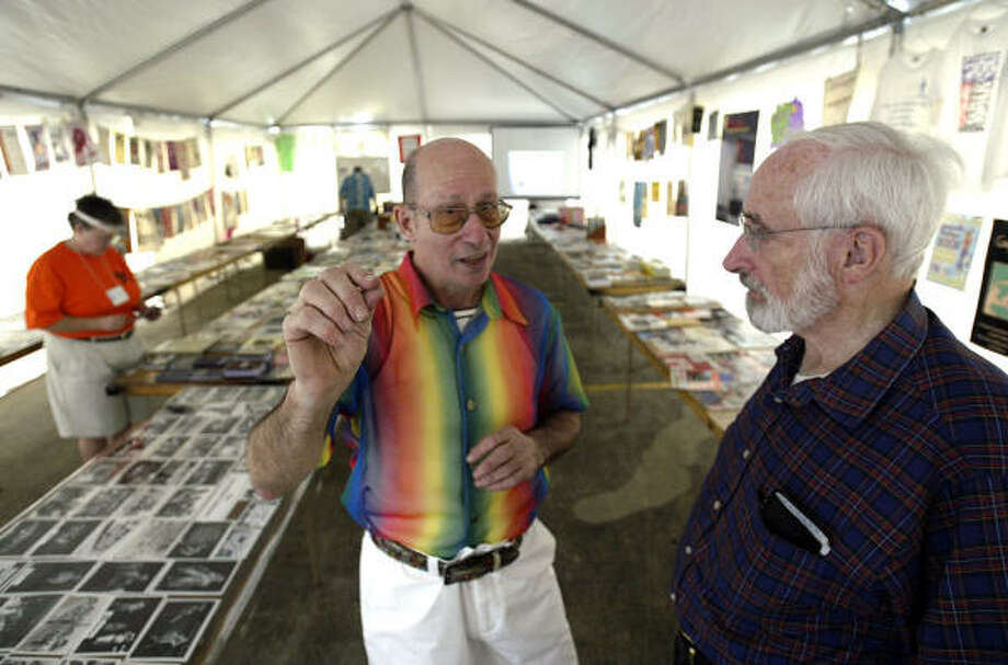Larry Criscione, center, curator of the Resurrection Metropolitan Community Church Gay History Tent, talks with the Rev. Ralph Lasher, right, of Bethel Lutheran Church, inside the exhibit tent. Photo: Jessica Kourkounis, For The Chronicle