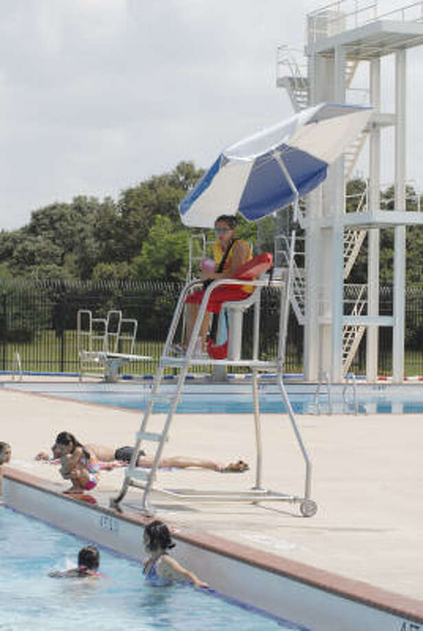 First year lifeguard Evelyn Ramirez watches over swimmers at the city of Houston's public pool at 10645 Hammerly. Photo: Tim Johnson, For The Chronicle