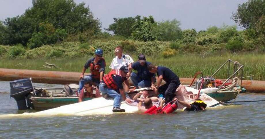 Rescuers pull Brian Stewart from the overturned boat after it struck a dredge line. Photo: Handout Photo