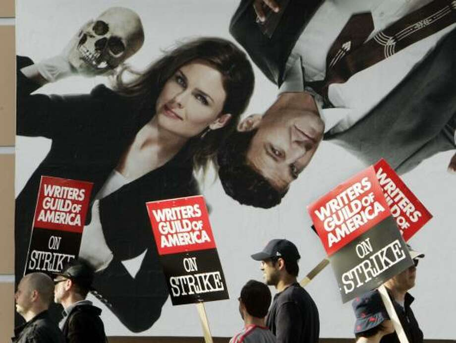 Striking Writers Guild members parade beneath a billboard for the Fox TV series Bones outside Twentieth-Century Fox Studios. Elsewhere, chanting writers with a bullhorn disrupted shooting for CBS' Cane. Photo: REED SAXON, ASSOCIATED PRESS