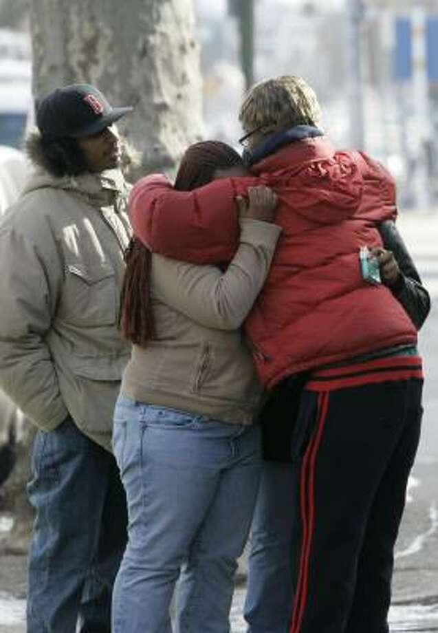Friends comfort each other near a boarded-up house that was destroyed by fire Sunday in West Philadelphia, killing four children and their mother. Photo: JACQUELINE LARMA, ASSOCIATED PRESS