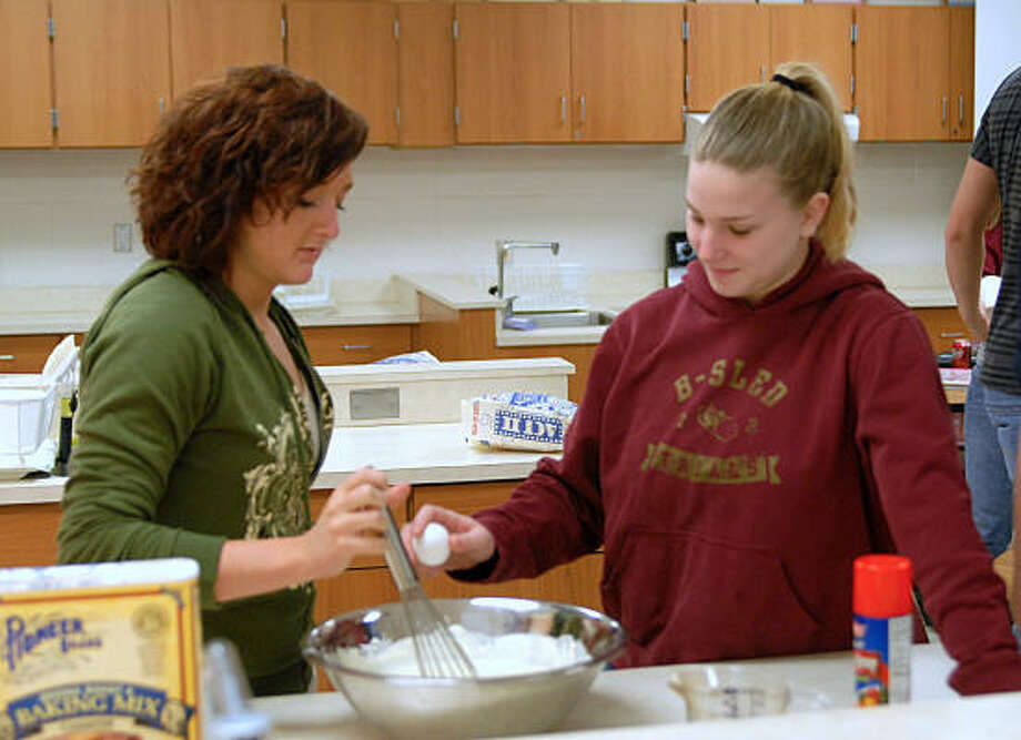 Elizabeth Mauldin stirs batter as Anna Brenner cracks another egg for the batter as they prepare pancakes for their cooking class at Magnolia High School. Photo: David Hopper, For The Chronicle