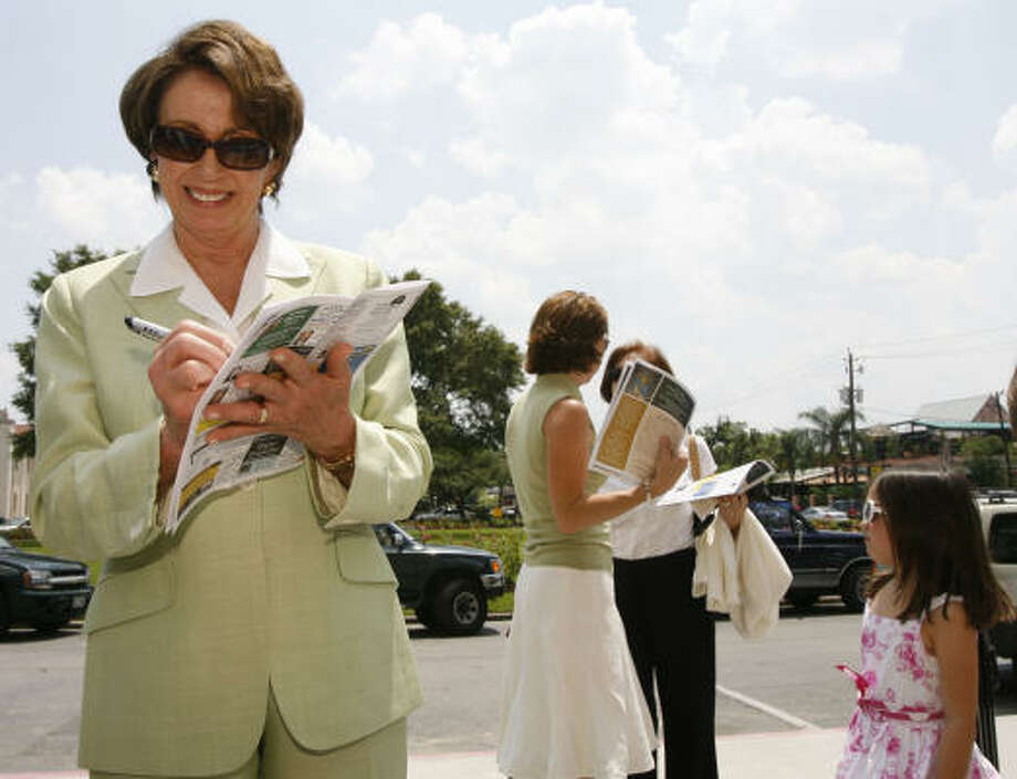 United States House Speaker Nancy Pelosi (left) signs an autograph outside St. Anne Catholic Church Sunday in Houston. Pelosi attended church services with her family. Photo: James Nielsen, Chronicle