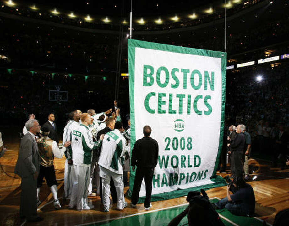 Boston Celtics players and team personnel gather to raise the Celtics' 17th NBA championship banner. Photo: Winslow Townson, AP