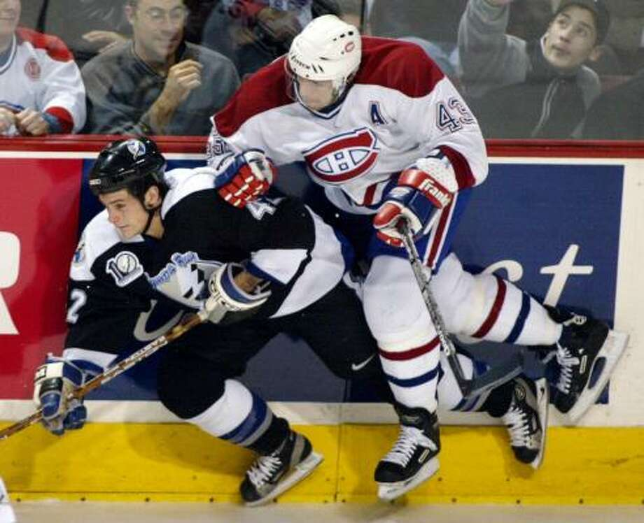 Montreal Canadiens Patrice Brisebois charges intoTampa Bay Lightning Sheldon Keefe during third period NHL action Monday, Dec. 17, 2001 in Montreal. The Lightning beat the Canadiens 4-3. (AP PHOTO/Paul Chiasson)   HOUCHRON CAPTION (12/18/2001):  Montreal's Patrice Brisebois runs Tampa Bay's Sheldon Keefe into the boards during the third period Monday night. Photo: PAUL CHIASSON, AP