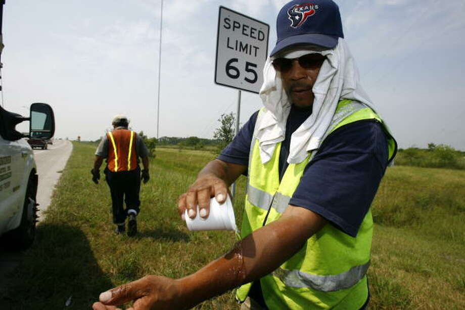 Bryan Jones tries to cool off with cold water as he takes a break from working on the Fort Bend Tollway on Monday. Photo: Nick De La Torre, Chronicle