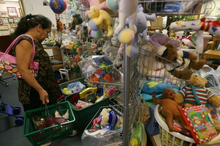 Olga Tellez shops through the toy section for her granddaughter at the Sunshine Resale Shop in Bellaire. The shop is one of several that have temporarily stopped accepting toys. Photo: MAYRA BELTRÁN, CHRONICLE