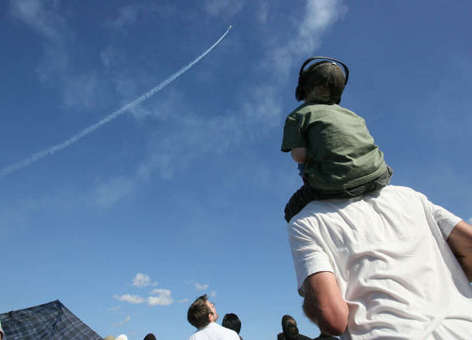 Jayden Gross, carried by his father Mark Gross, watches the USAF Thunderbirds perform aerial maneuvers at the 24th Annual Ron Carter Wings Over Houston Air show at Ellington Field on Sunday. Photo: Mayra Beltran, Chronicle