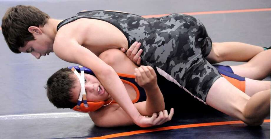 Christopher Bryant, 13, bottom, of Danbury, representing the West, wrestles and loses the 112 lb. match against Eric Manuel, of the South, during the Nutmeg Games at Danbury High on sunday. Photo: Michael Duffy / The News-Times