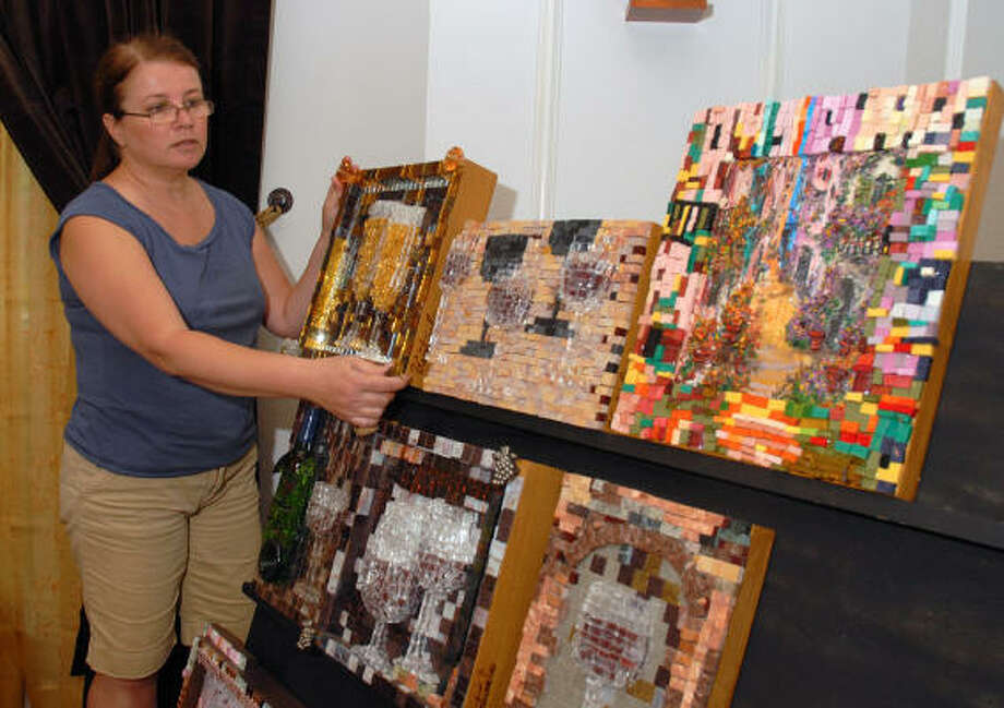 The Woodlands artist Kathy Steigert puts the finishing touches on a display of her artwork. Photo: David Hopper, For The Chronicle