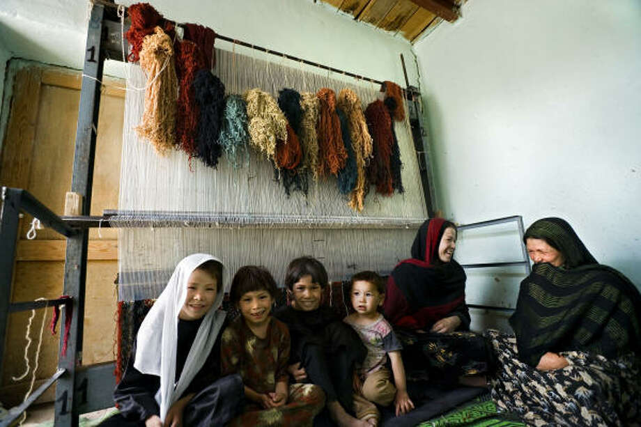 Women in Afghanistan, children at their side, can make money weaving rugs for Arzu Inc. Photo: Thomas Lee