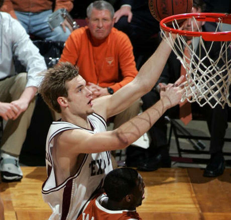 Texas A&M's Antanas Kavaliauskas, top, goes for the basket over Texas' Damion James. Photo: Paul Zoeller, AP