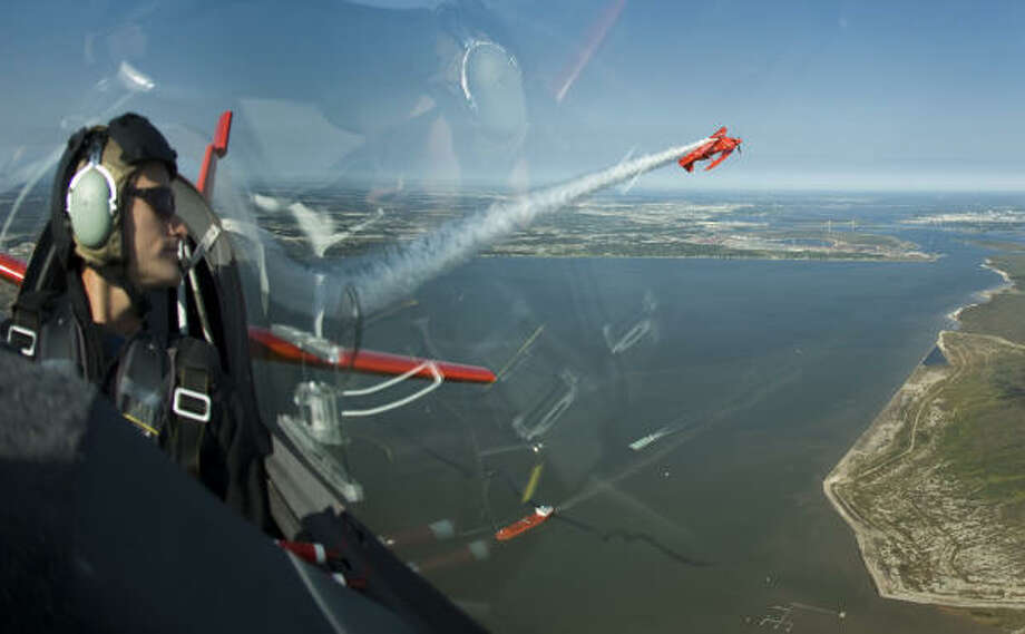 Eric Tucker keeps an eye on his father, Sean Tucker as they fly aerobatic formations over the Galveston Bay, Thursday, as a warmup to this weekend's Wings Over Houston Airshow at Ellington Field. Photo: Steve Ueckert, Chronicle