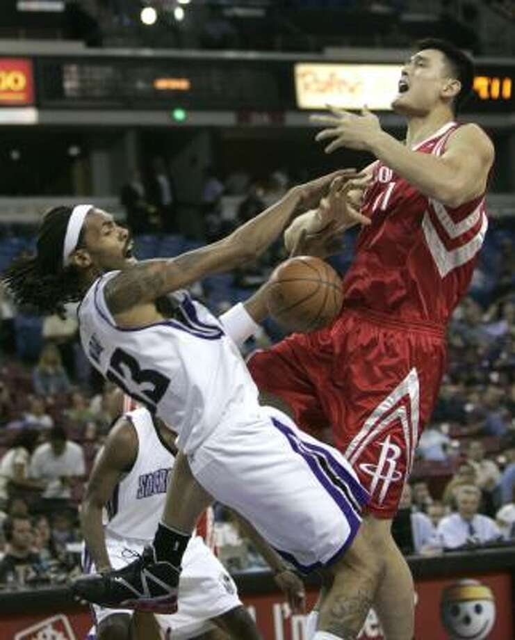 Yao Ming, right, is fouled by Kings forward Mikki Moore during the first quarter. Photo: Rich Pedroncelli, AP