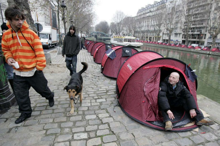 A homeless person sits in a tent along the Saint-Martin canal in Paris More than 100 tents for homeless people were set up to raise awareness of homelessness. Photo: FRANCOIS MORI, ASSOCIATED PRESS