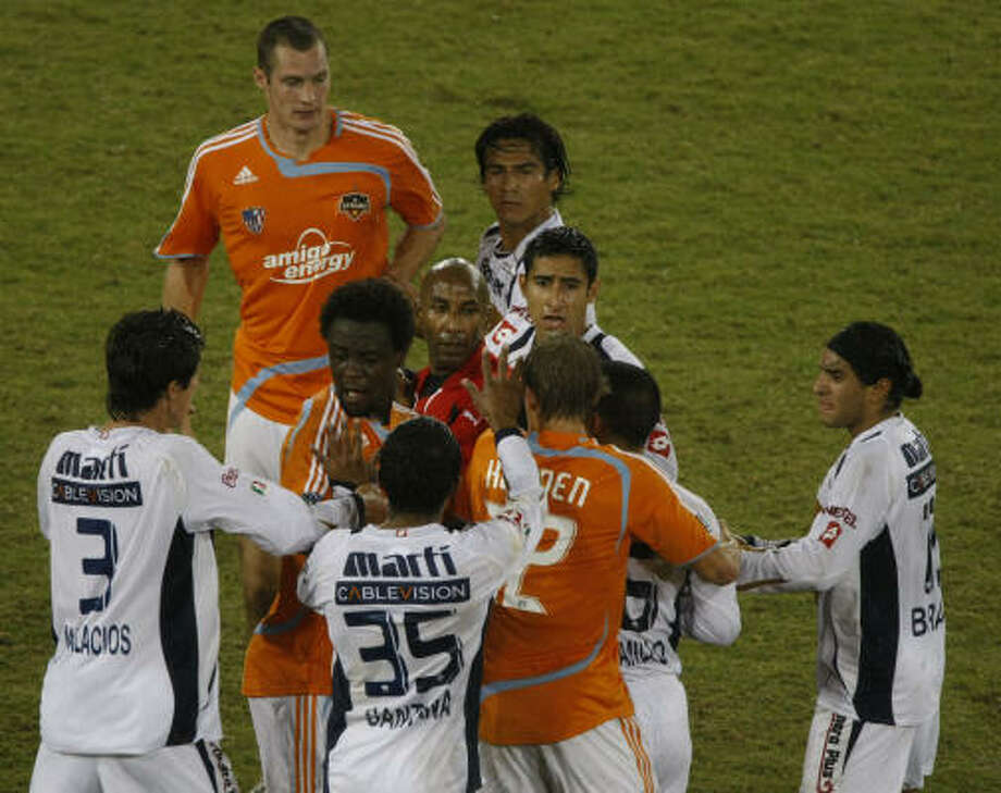 Referee Neal Brizan, center, tries to control a situation where Dynamo players and Pumas players pushed and shoved in the first half. Photo: Julio Cortez, Chronicle