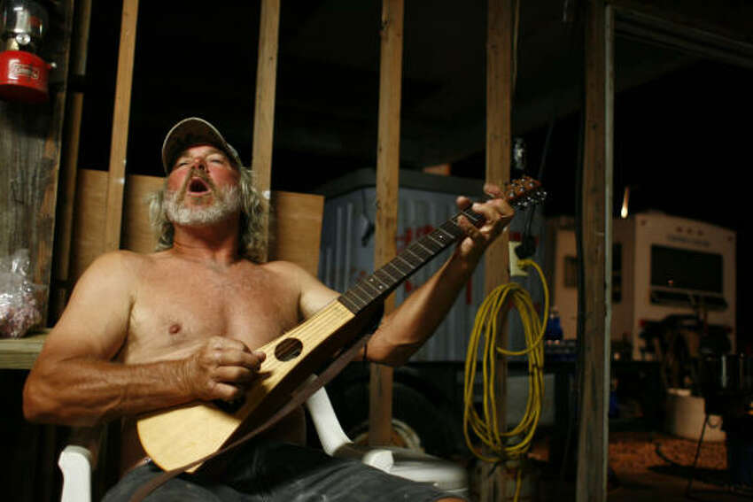 Cornell Strimple plays a song to entertain fellow Bolivar residents at Peninsula Marine Inc. & Marine Towing and Salvage on Oct. 21.