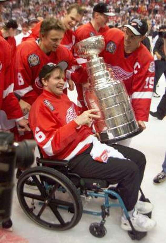Red Wings captain Steve Yzerman, right, and Igor Larionov, left, wheel teammate Vladimir Konstantinov around the ice for his turn with the Stanley Cup after Detroit beat the Washington Capitals in Game 4 of the 1998 Stanley Cup Finals. Photo: PAUL CHIASSON, AP