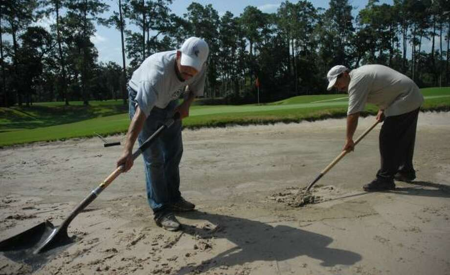 Oscar Solorio, left and Fabian Amador repair a sand bunker at Cypresswood Golf Club, where heavy rain sometimes causes the sand to wash out of the bunkers. Photo: MEGAN TRUE, CHRONICLE