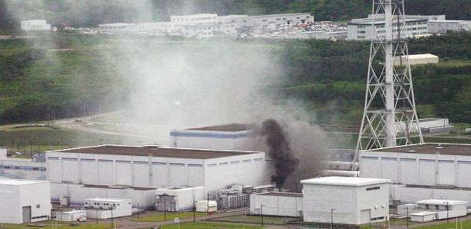 Black smoke rises near one of Kashiwazaki Kirawa nuclear power plant's four reactors after a quake on the northwest coast of Japan, about 160 miles from Tokyo. Photo: JAPAN COAST GUARD, AP