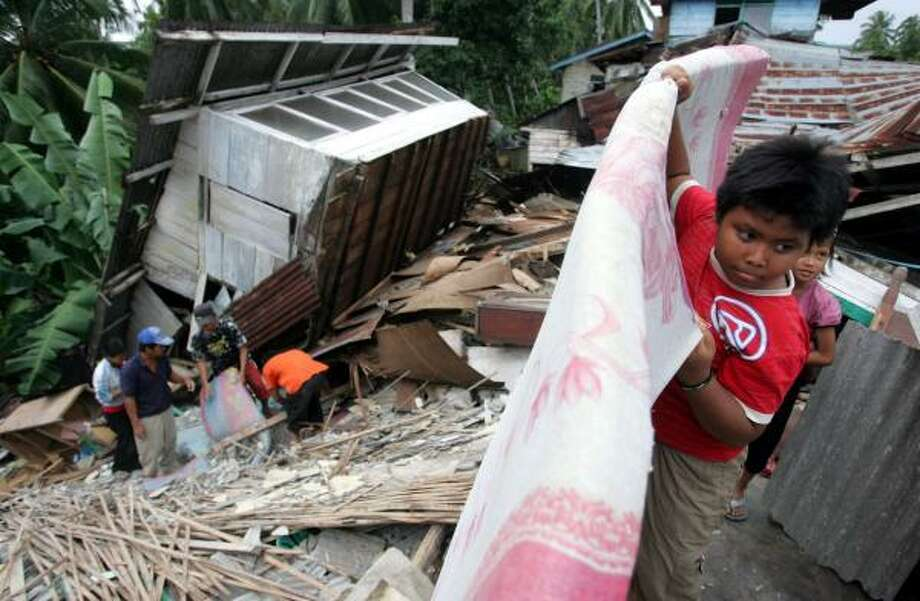 An Indonesian boy retrieves a mattress from his house destroyed by an earthquake in Bengkulu, on Sumatra Island, Indonesia. The island escaped the full force of a tsunami created by the undersea quake. Photo: DITA ALANGKARA, ASSOCIATED PRESS