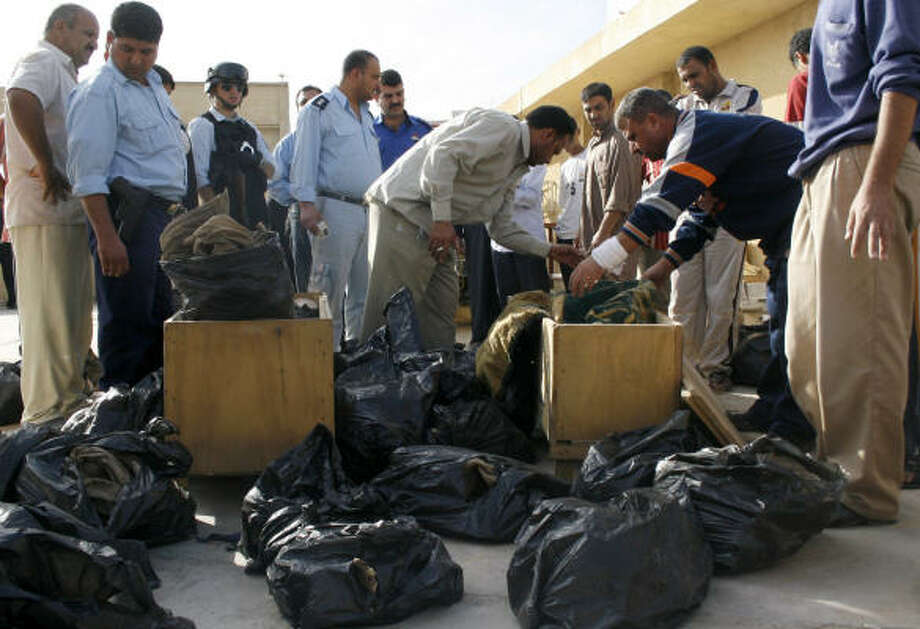 Iraqis examine bags holding the human remains found in southern Baghdad on today. Photo: LOAY HAMEED, Associated Press