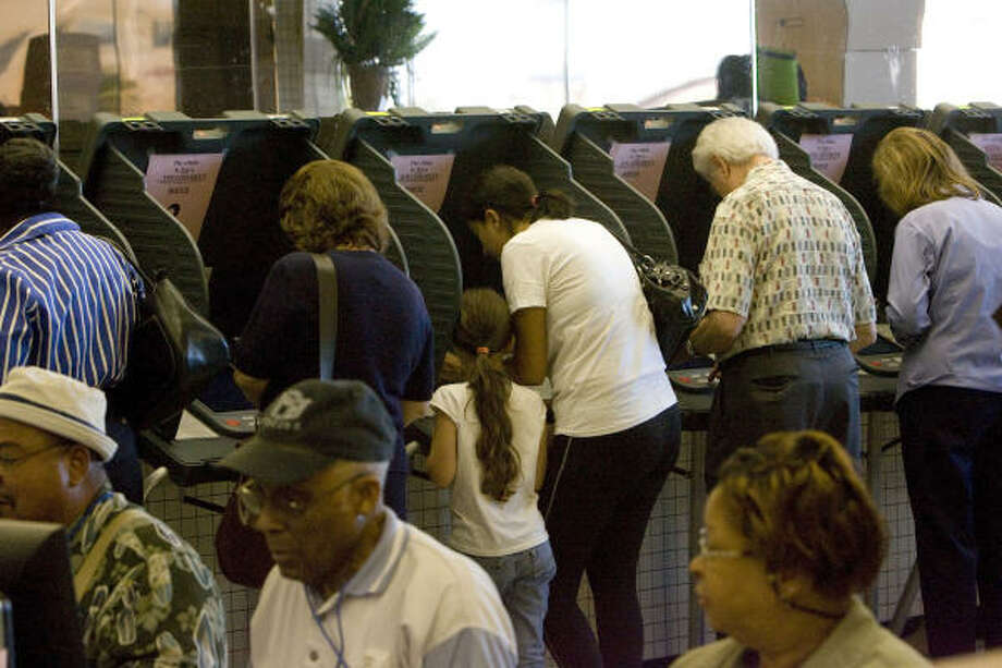 Early voters cast their votes today at a Fiesta grocery store on the 8100 block of Kirby during the first day of early voting. Photo: Johnny Hanson, Chronicle