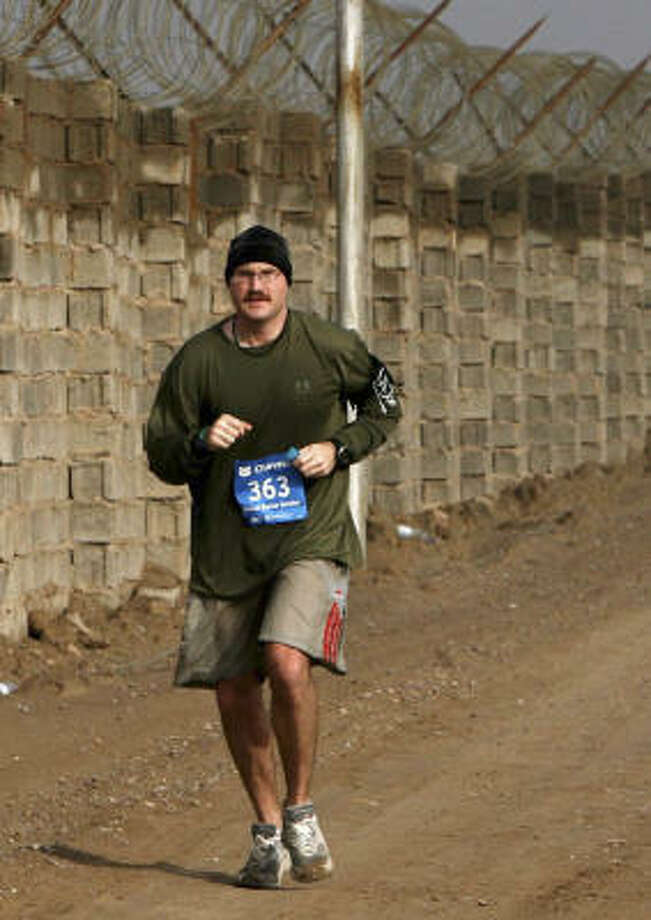 A Marine runs along a fence line during the Satellite Chevron Houston Marathon run in Camp Fallujah, Iraq. Since many soldiers couldn't come to the race, a version of the race came to them. Photo: Cpl. Lynn Murillo, USMC
