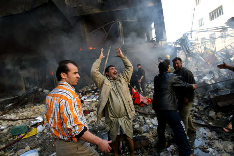 Iraqis grieve in front of a burning building after a double car bomb attack in central Baghdad Monday. Photo: KHALID MOHAMMED, AP