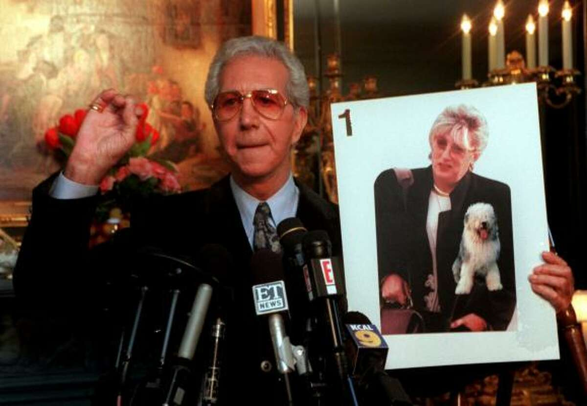 Mr. Blackwell holds a photo of Clinton-Lewinsky scandal figure Linda Tripp as he comments: