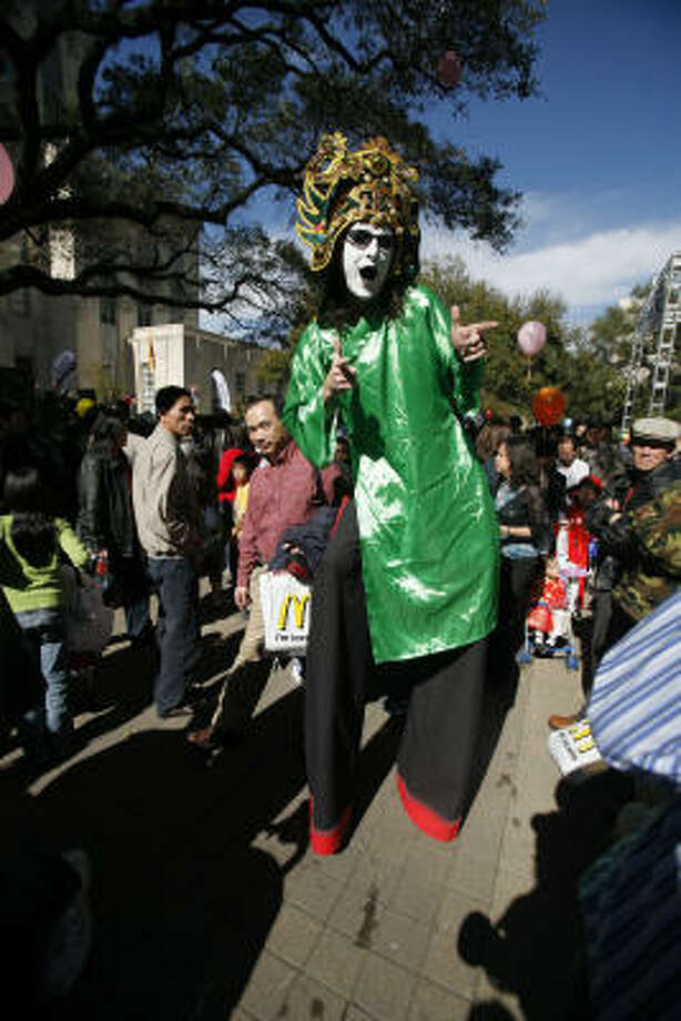Robert Edmonsond walks through the crowd on stilts in a traditional Asian costume at the Lunar New Year festival in Hermann Square. The festival included a children's Vietnamese costume and culture competition, food, games and entertainment. Photo: Steve Campbell, Chronicle