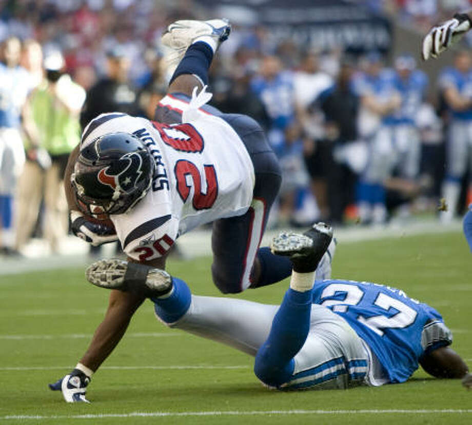 Houston Texans running back Steve Slaton dives over Detroit Lions safety Daniel Bullocks. Photo: Brett Coomer, Chronicle