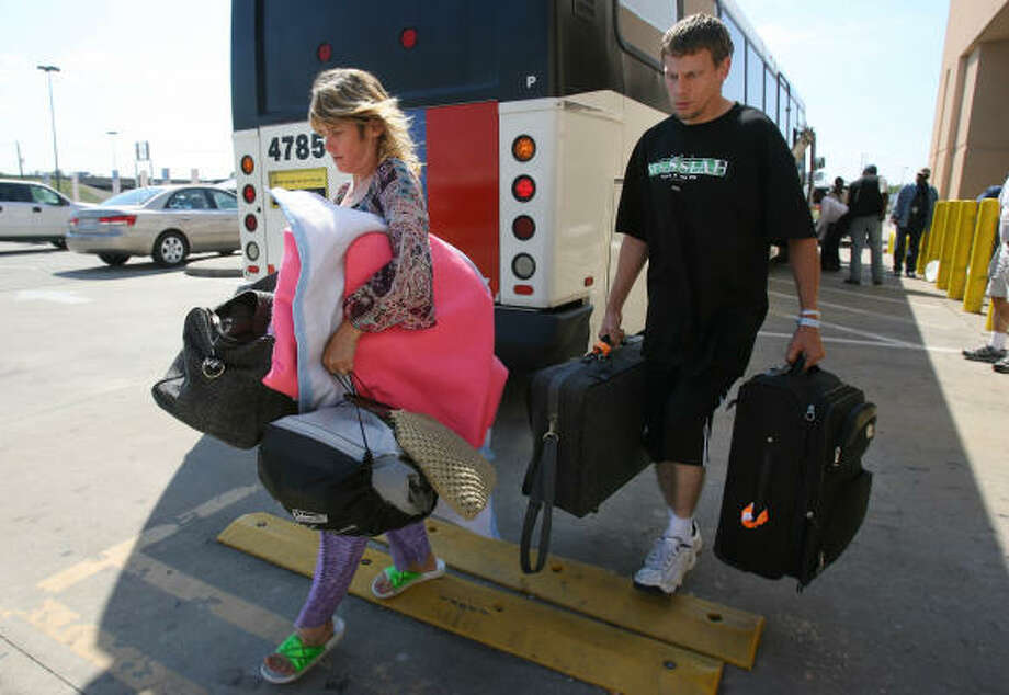 Gloria and Kevin Bradford carry personal items toward a vehicle that will take them to their new apartment in La Porte. Gloria plans to work at Taco Bell while Kevin works contract jobs in La Porte. Photo: Mayra Beltran, Chronicle