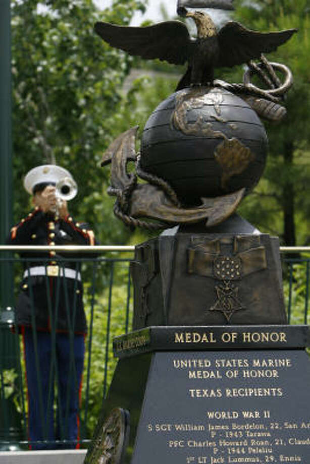 Taps is played during a dedication ceremony of the monument honoring Texas Marine Medal of Honor recipients in The Woodlands on Friday. Photo: Melissa Phillip, Chronicle