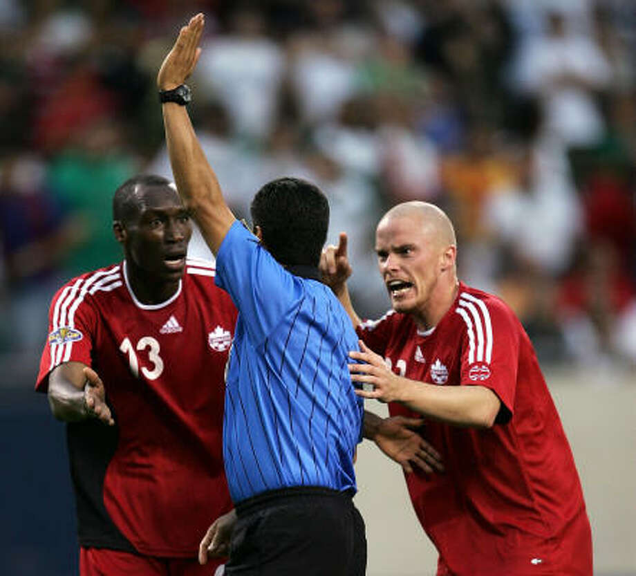 Canada's Atiba Hutchinson, left, and Iain Hume plead their case to referee Benito Archundia after an apparent goal scored by Hutchinson was disallowed late in the Americans' 2-1 victory. Photo: Jonathan Daniel, Getty Images
