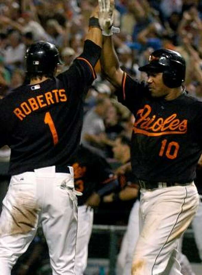 Miguel Tejada, right, congratulates Brian Roberts after Roberts scored the Orioles' game-winning run. Photo: GREG FIUME, GETTY