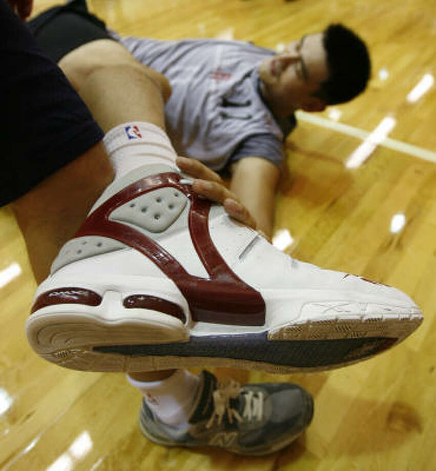 Rockets center Yao Ming stretches after training camp Friday at the University of Texas' Cooley Pavilion in Austin. Photo: Kevin Fujii, Chronicle