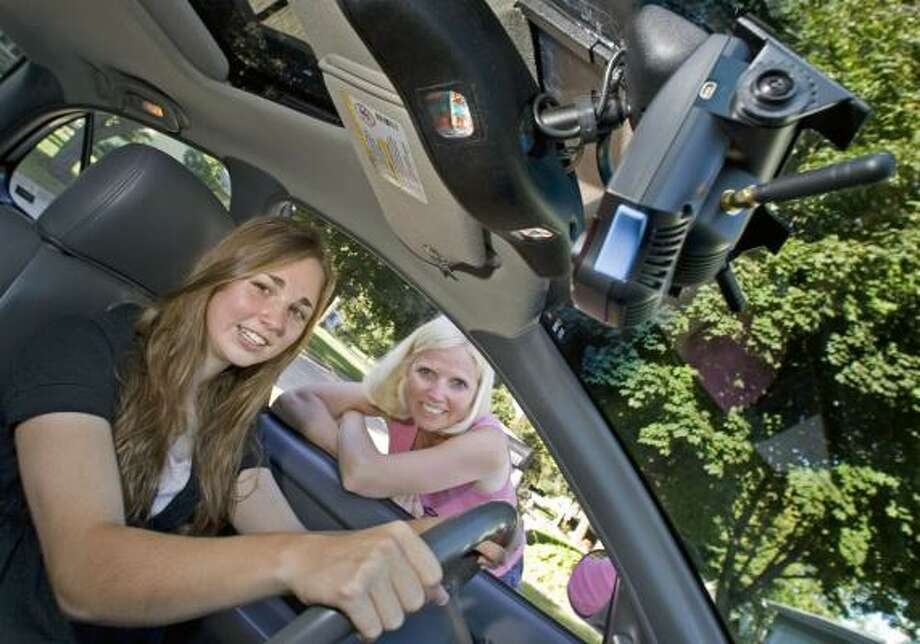 Anna Kinderman, 17, and her mother, Bette Kinderman, show the small camera installed near the rearview mirror to record unsafe events when the Madison, Wis., teenager drives. Photo: ANDY MANIS, ASSOCIATED PRESS